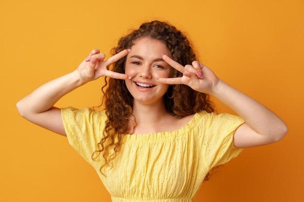 Портрет молодой смешной женщины, показывающей жест мира