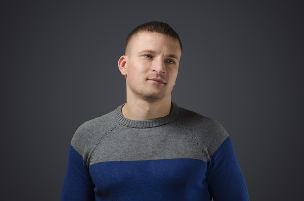 笑顔の若いゲイの男性の肖像画。黒い表面のスタジオでの感情的な写真