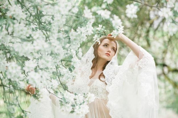 Портрет молодой девушки на фоне цветущих садов. естественный макияж, прическа.