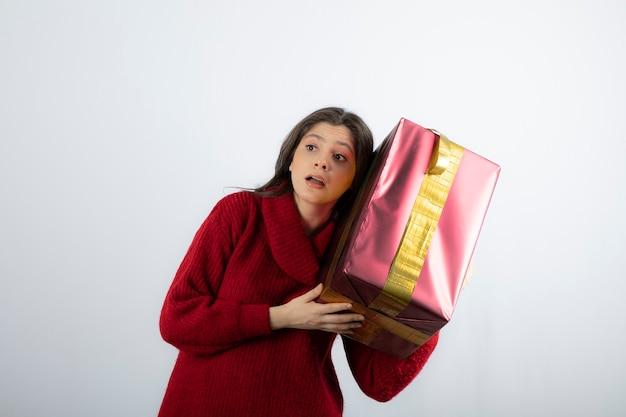 스웨터를 입고 선물 상자를 들고 있는 어린 소녀의 초상화.