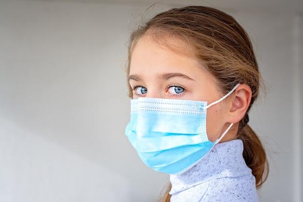 Портрет молодой девушки в медицинской маске крупным планом.