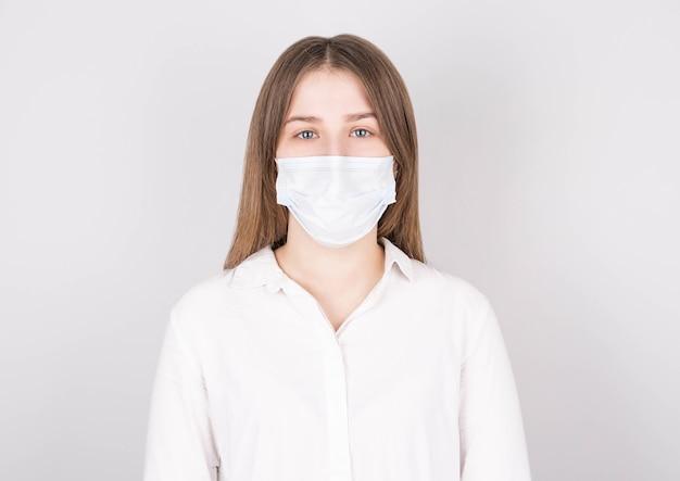 흰 벽에 고립 된 의료 마스크에 젊은 여자의 초상화.