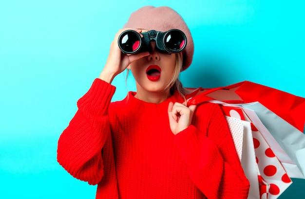 Bonocular 상자와 파란색 배경에 쇼핑백 빨간 스웨터에 젊은 여자의 초상화