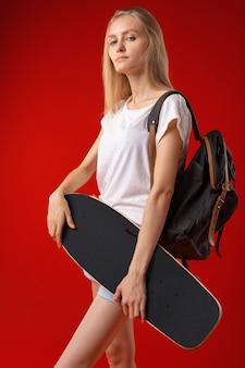Портрет молодой девушки в коротких шортах с лонгбордом