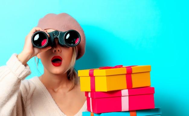 파란색 배경에 쌍안경 및 선물 상자와 흰색 스웨터에 어린 소녀의 초상화