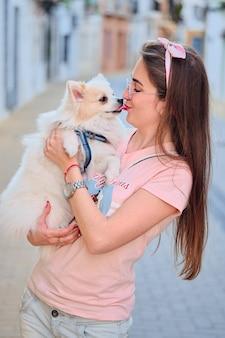 彼女の白いふわふわポメラニアン犬にキス若い女の子の肖像画。 Premium写真