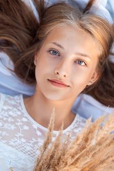 ドライフラワーの花束と白い布の上に横たわる少女の肖像画。