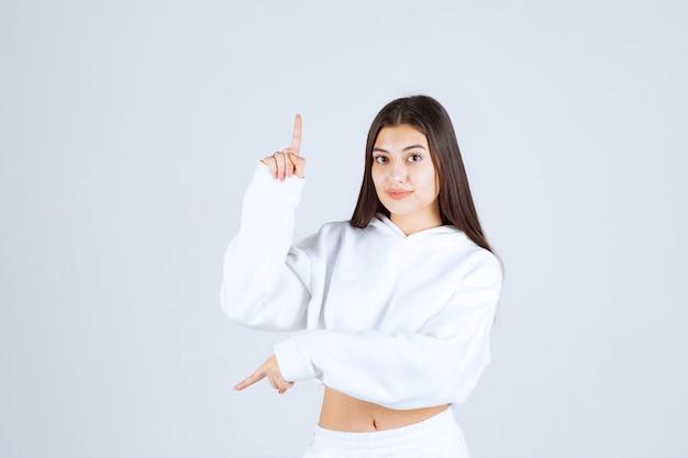 Портрет модели молодой девушки указывая вверх и вниз.
