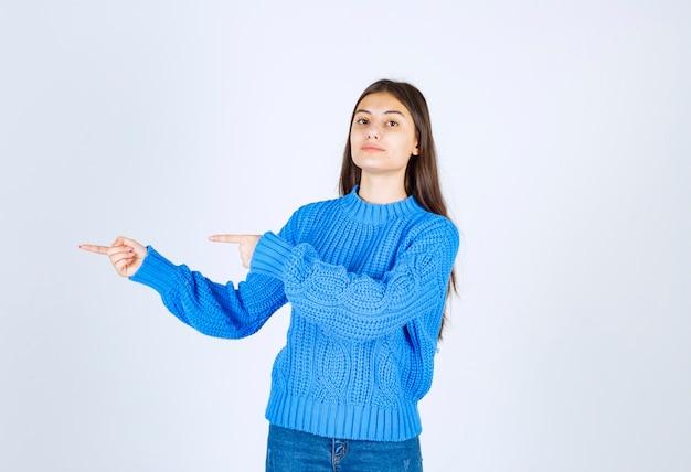 立って、離れて指している若い女の子モデルの肖像画。