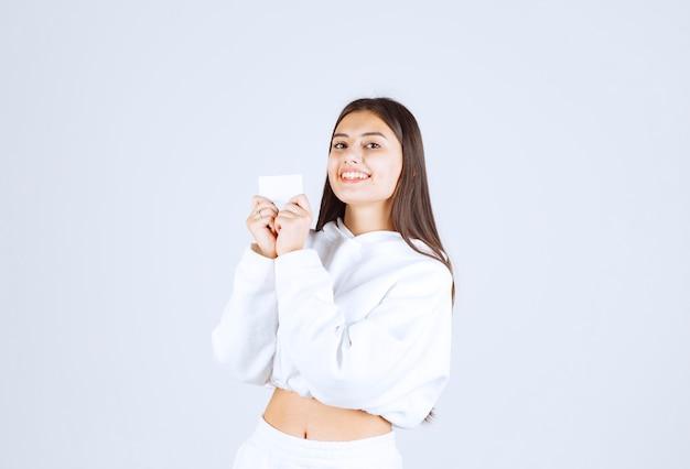白灰色の背景にカードを持つ少女モデルの肖像画。