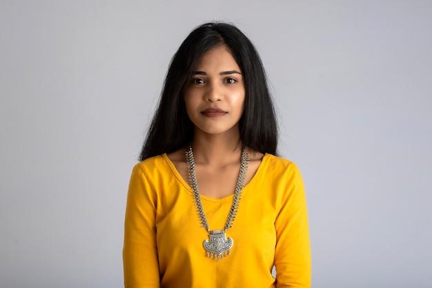 Портрет молодой девушки, позирующей на сером