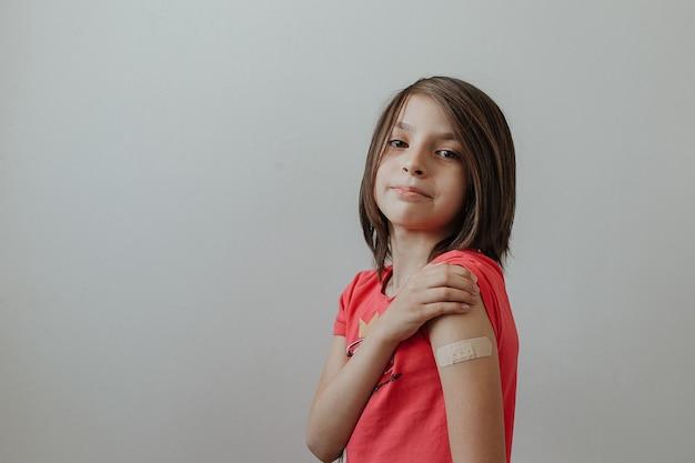 코로나바이러스 covid19에 대한 백신을 맞은 후 패치가 있는 팔을 보여주는 어린 소녀의 초상화