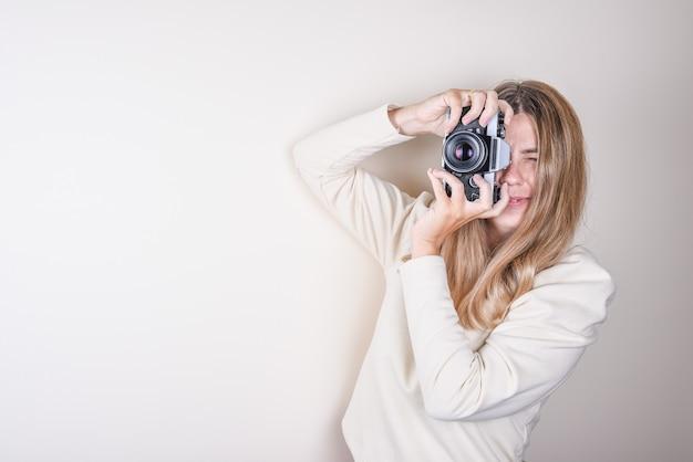 Портрет молодой девушки, фотографирующей на профессиональный фотоаппарат