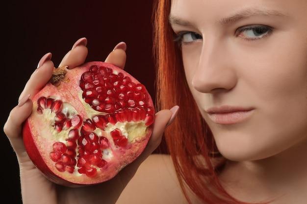 赤い背景の手に赤い髪とザクロの果実を持つ少女の肖像画