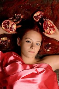 赤い髪と茶色の背景に彼女の髪にザクロの果実を持つ少女の肖像画