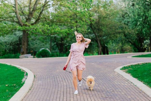 手に彼女のかわいいポメラニアンスピッツを保持しているピンクのドレスを着ている若い魅力的な女性の肖像画。 。犬と人間のコンセプトの友情。