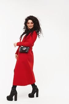 Портрет молодой великолепной женщины в красном пальто и сапогах на высоких каблуках