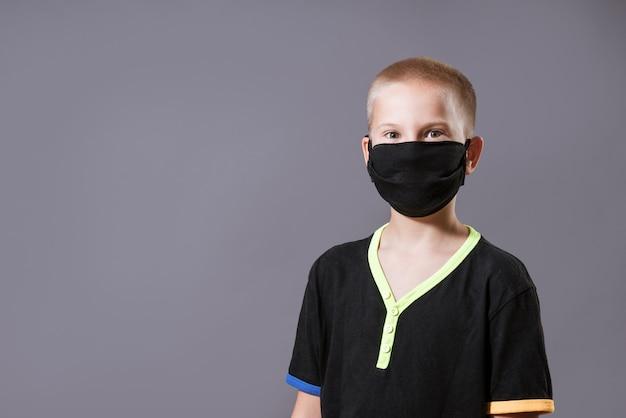 灰色の壁に黒い保護マスクとtシャツを着た若い男の肖像画