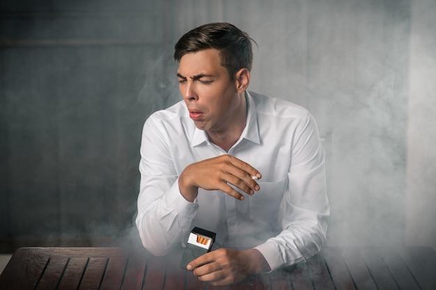 煙のような背景に対してポーズをとって、タバコのパックを手に持ち、火をつけた葉巻を手から持ち、咳をする若い男の肖像画。肺の病気。たばこ咳。