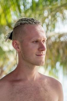 자연 속에서 그의 머리에 향취를 가진 젊은 남자의 초상화. 열 대 해변에서 향취와 행복 잘생긴 남자를 닫습니다