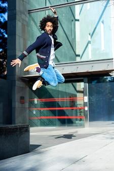 晴れた日に屋外で笑顔のカメラを見ながらジャンプする若いハンサムなアフロ黒人男性の肖像画