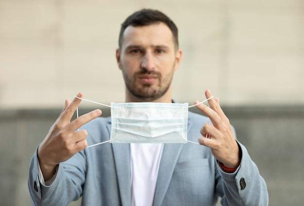 手に医療フェイスマスクを保持している若いハンサムなブルネットの男の肖像画