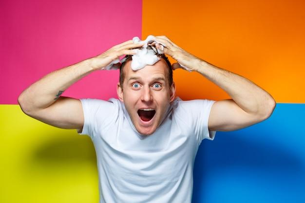 Портрет молодого красивого жизнерадостного парня на разноцветном фоне, одетого в белую футболку, создает модную прическу, глупые и положительные эмоции.