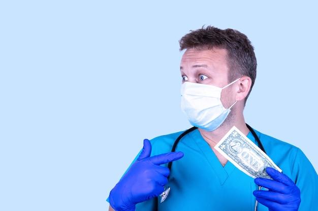 明るい背景に1ドル紙幣を持つ若いハンサムな医者の肖像画。医療給与の概念。