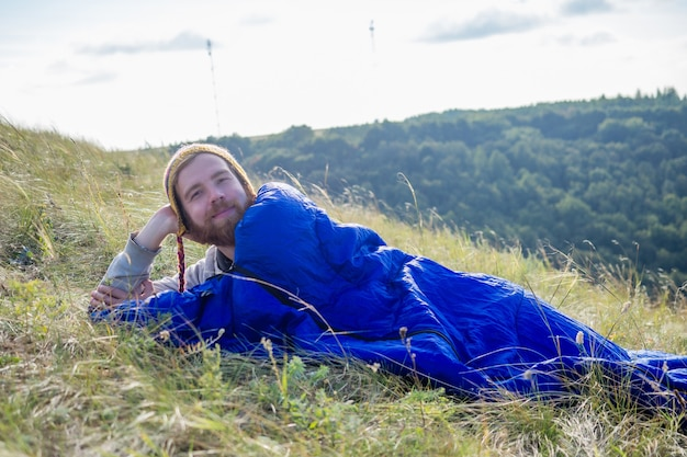 Портрет молодого красивого туриста с рыжеволосой бородой в забавной шапке из шерсти яка, связанной из непала на природе, лежащей в синем спальном мешке, пейзаж озеро и холмы