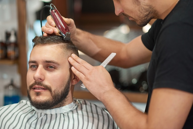 理髪店で新しい散髪を楽しんでいる若いハンサムな男の肖像画。