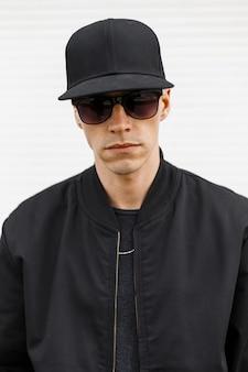 Портрет хипстера молодого красивого человека в черной кепке, в стильных черных очках в модной осенней куртке-бомбардировщике на белой стене. американский привлекательный парень.