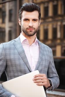 Портрет молодой красавец в куртке держит ноутбук