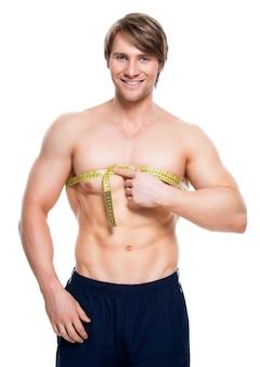 Портрет молодого красивого человека с мускулистым торсом использует измерительную ленту на белой стене.