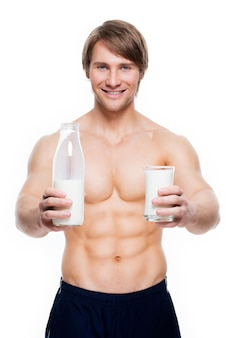 Портрет молодого красивого мускулистого мужчины держит молоко - изолированное на белой стене.