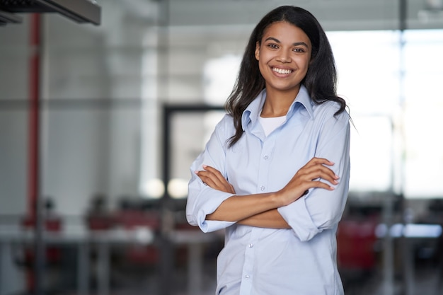 Портрет молодой счастливой привлекательной деловой женщины или офисного работника, скрестив руки