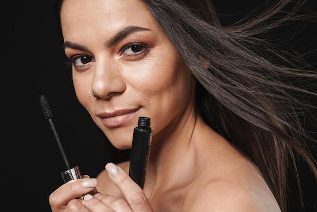 Портрет молодой счастливой красивой обнаженной женщины, позирующей изолированной над черной стеной, держащей тушь, наносит макияж.