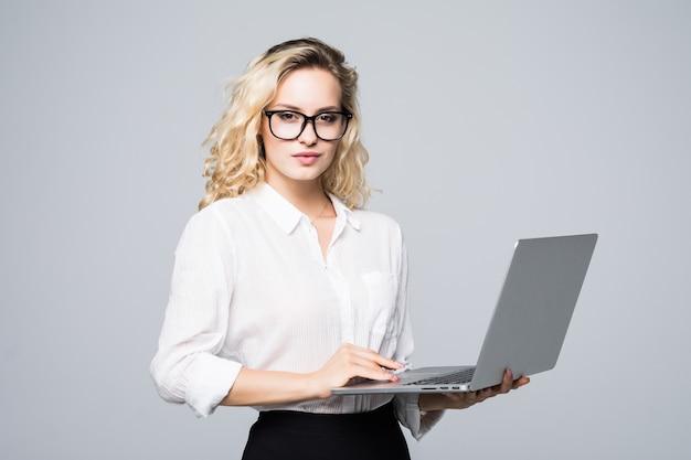 Портрет молодой счастливой деловой женщины с ноутбуком над белой стеной