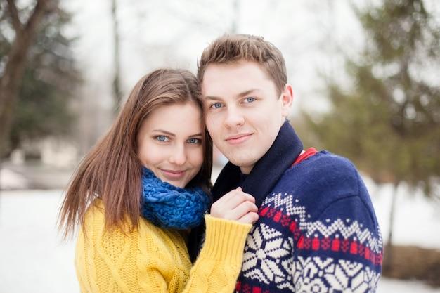 色のセーターで若い幸せなカップルの肖像画