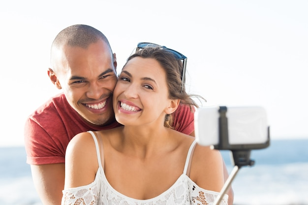 ビーチで自撮り棒でselfieを取る若い幸せなカップルの肖像画