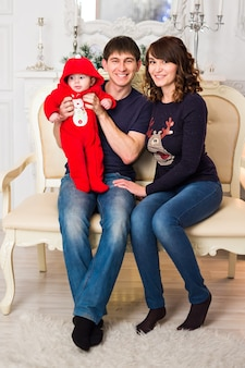 Портрет молодой счастливой семьи с ребенком дома.