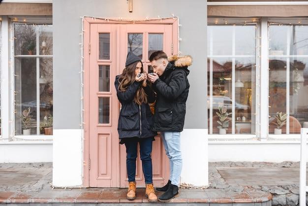 Портрет молодой счастливой любящей пары, стоящей возле кафе на открытом воздухе, пить кофе.