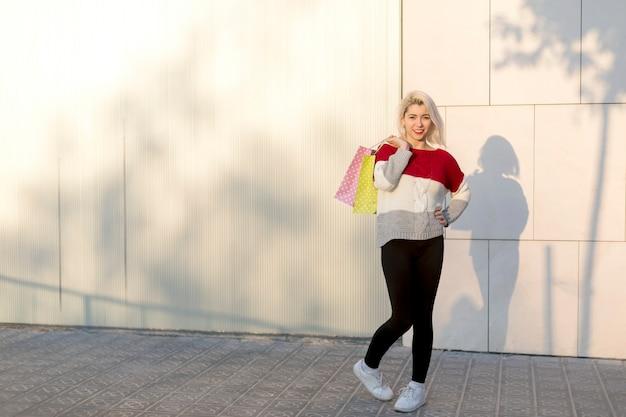 Портрет молодой счастливой улыбающейся женщины с хозяйственными сумками