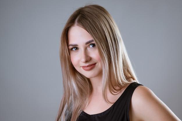 明るい壁にポーズをとって黒いtシャツを着た若い幸せな女性の肖像画