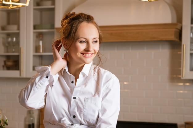 측면을 찾고 부엌에서 흰 셔츠에 젊은 행복한 여자의 초상화
