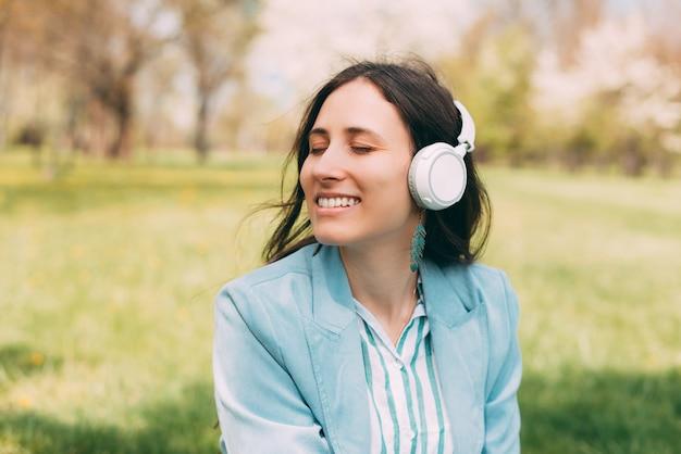 Портрет молодой счастливой женщины, слушающей музыку в наушниках