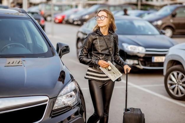 야외 주차장에 임대 계약과 여행 가방을 들고 서 있는 행복한 젊은 여성의 초상화