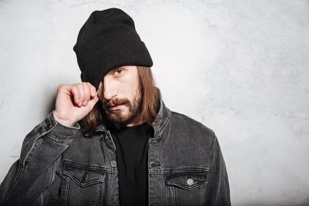 Портрет молодого хипстерского мужчины с бородой, позирующего и смотрящего вперед, изолированного за стеной