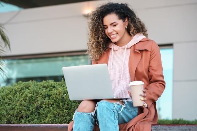 彼女のラップトップを使用して、屋外に座ってコーヒーを飲む若いラテン女性の肖像画。アーバンコンセプト。