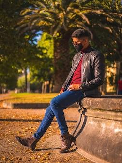 噴水で街の若いラテン系アメリカ人の肖像画。ジーンズ、革のジャケット、茶色の靴