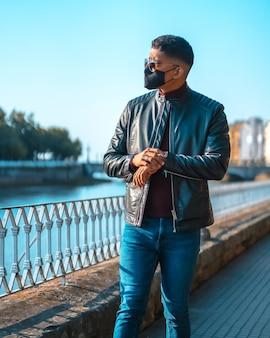 街の川にいる若いラテン系アメリカ人の肖像画。ジーンズ、革のジャケット、茶色の靴